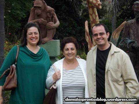 Pose em família diante de estátuas de animais.